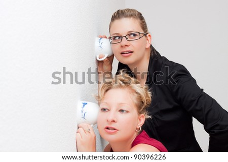 Funny moment of two young women listening through the wall. - stock photo