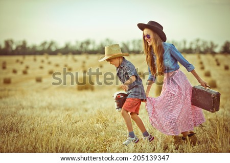 Funny mother and a son in cowboy hats playing in travelers with a toy horse outdoors. in motion. toned old vintage image - stock photo