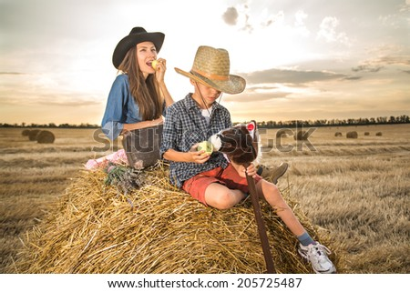 Funny mother and a son in cowboy hats travelers relaxing on hay roll eating an apple. focus on cute boy feeding his toy horse - stock photo