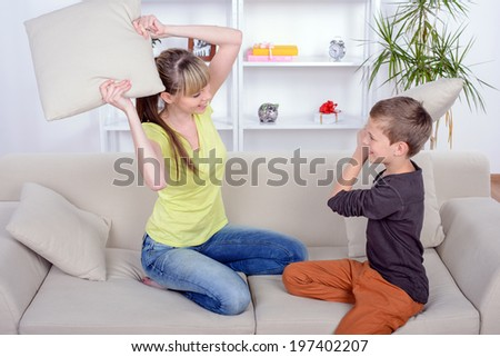 Funny Mother and Son battle the pillows on the couch at home - stock photo