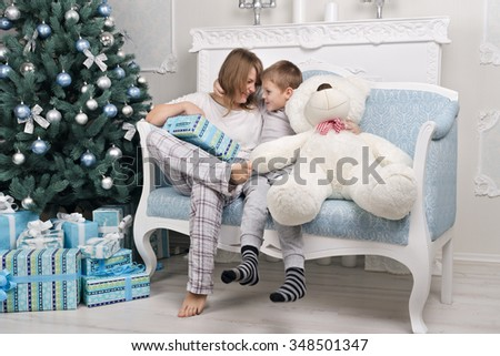 Funny mother and son in pajamas without a dad sitting with a gift near the Christmas tree. Toy instead Pope. Christmas Tree. Christmas scene. Christmas gifts. Christmas and New Year without a dad. - stock photo