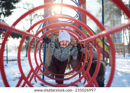 funny mother with her son playing in winter park and show tongues - stock photo