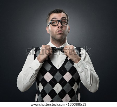 Funny nerd preparing to go out for a date isolated over dark gray textured background - stock photo