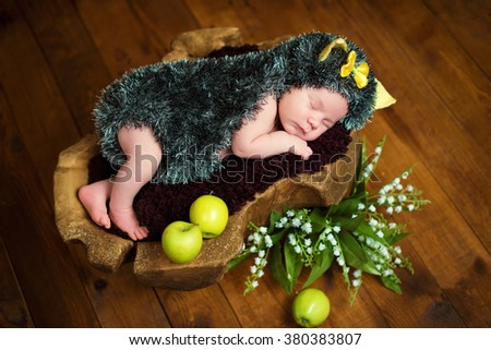 Funny newborn little baby girl in a costume of hedgehog sleeping sweetly on the stump - stock photo