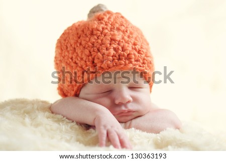 funny newborn wearing pumpkin hat - stock photo