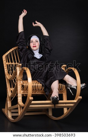 Funny nun wearing headphones and waving his hands to the music while sitting in a rocking chair - stock photo
