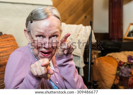 Funny old woman in pink sweater showing dance style hand gesture - stock photo