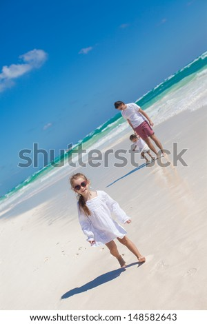 Funny older daughter in the foreground and dad with youngest daughter in the background on the beach - stock photo