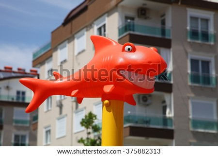 Funny orange shark with snow-white smile in the sunshine - stock photo