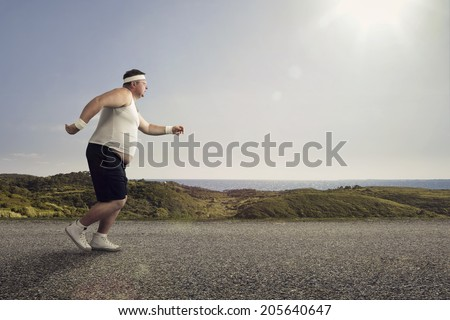 Funny overweight man jogging on the road - stock photo