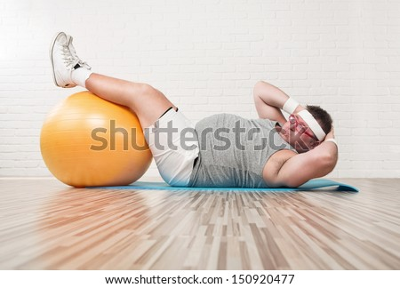 Funny overweight man working out on the floor - stock photo