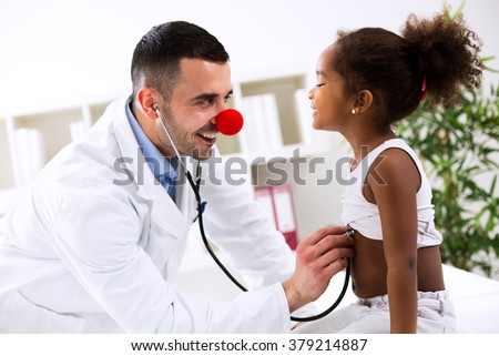 Funny pediatrician with little cute child in office - stock photo