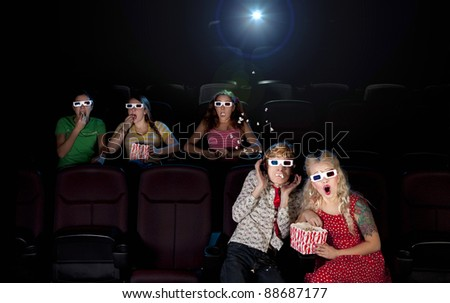 Funny people are watching scary 3d movie - popcorn is flying - stock photo