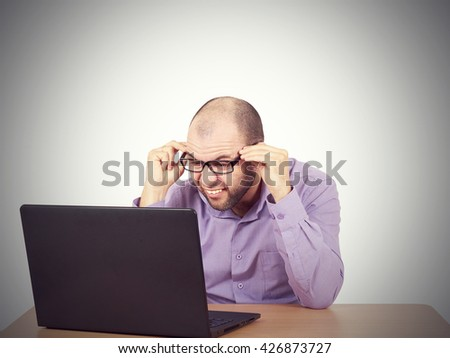 Funny photo of businessman bald with beard wearing shirt and glasses.  angry businessman working with laptop at table. Isolated on white background  - stock photo