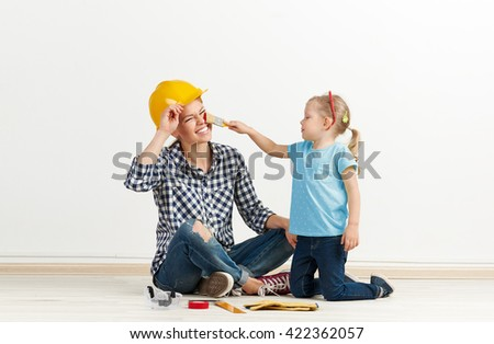 Funny picture of laughing female in protective helmet and little girl with paintbrush. Concept of house remodeling and repair.  - stock photo