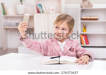 Funny picture of little cute girl playing role of business woman. Girl wearing pink suit. Girl sitting at table with notebook and making photo by phone. Office interior as a background - stock photo