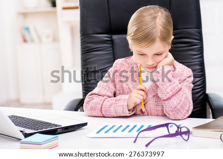 Funny picture of little cute girl playing role of business woman. Girl wearing pink suit. Girl sitting at table on large office chair and examining graph. Office interior as a background - stock photo