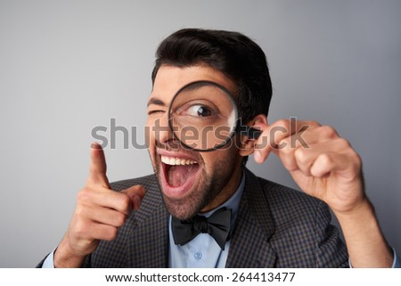 Funny picture of positive casual young man wearing jacket and bow tie. Man smiling, holding magnifier near eye and pointing at camera - stock photo
