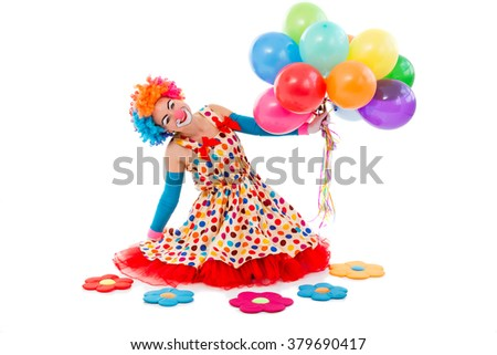Funny playful female clown in colorful wig holding balloons, looking at camera and smiling, sitting near toy flowers isolated on a white background - stock photo