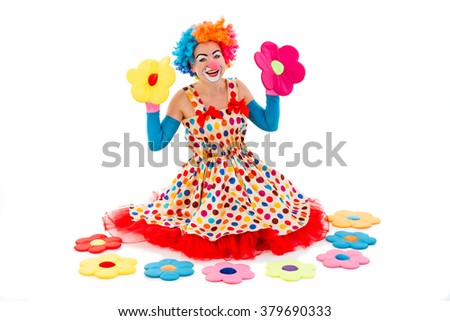 Funny playful female clown in colorful wig holding toy flowers in both hands, looking at camera and smiling, sitting near toy flowers isolated on a white background - stock photo