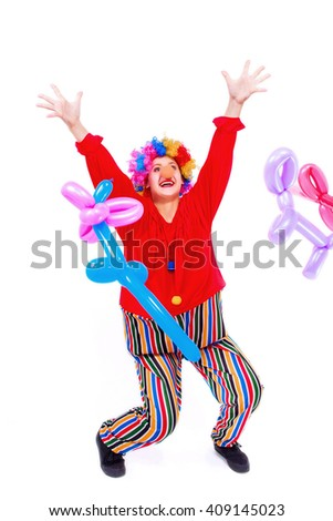 Funny playful girl clown in colorful wig throws up a balloons, isolated on a white background. Clown in the costume - stock photo