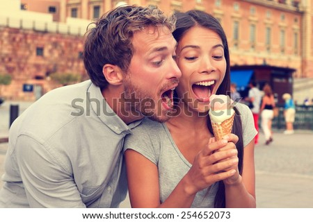 Funny playful young couple eating ice cream. Goofy portrait of boyfriend teasing girlfriend biting off a cold dessert in city summer, Stockholm, Sweden, Europe. - stock photo