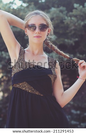 funny portrait of a beautiful girl in stylish fashion sunglasses outdoors. - stock photo