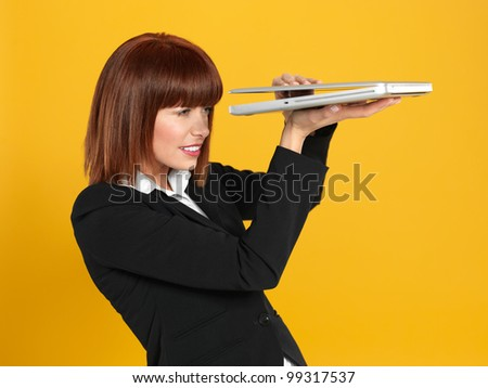 funny portrait of a beautiful, young businesswoman, holding a laptop, peeping to see the screen , on yellow background - stock photo