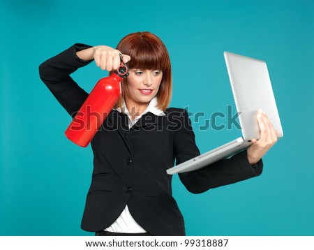 funny portrait of a beautiful, young businesswoman, using a fire extinguisher on her laptop, on blue background - stock photo