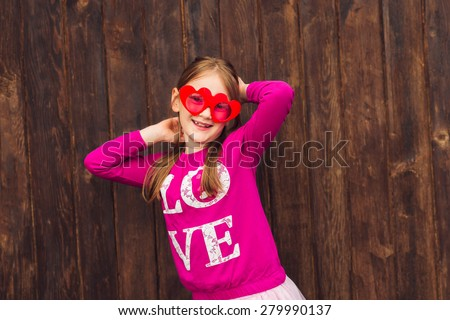 Funny portrait of a cute little girl wearing big heart shaped sunglasses - stock photo