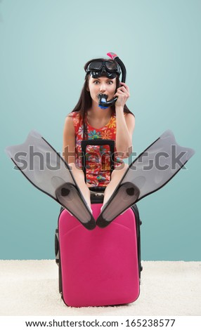 Funny portrait of a girl going on a vacation with her travel luggage and snorkeling equipment, on blue background - stock photo