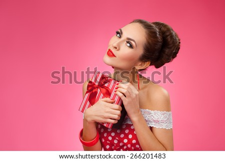 Funny portrait of a smiling cute young female model embraces gift box. Pink Background - stock photo