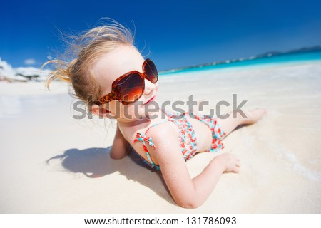 Funny portrait of adorable little girl at tropical beach - stock photo