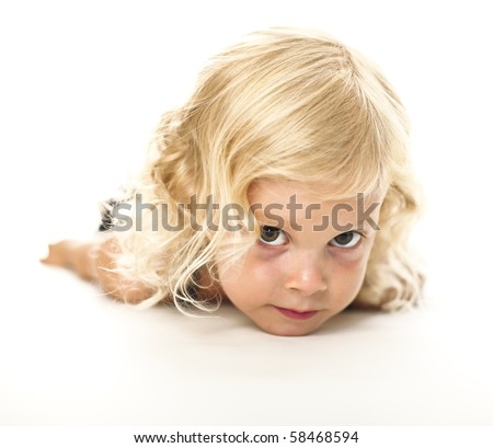 funny portrait of blond adorable little lay down girl - stock photo