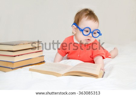 funny portrait of cute  baby in glasses lying over a big book - stock photo