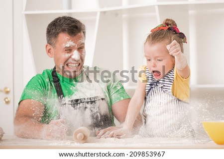Funny portrait of cute little daughter with handsome father cooking pastry, working with rolling pin and throwing flour. Dirty aprons - stock photo