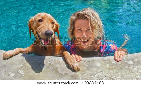 Funny portrait of smiling woman playing with dog and training golden retriever puppy in blue swimming pool. Popular dog breeds, outdoor activity and fun games with family pet on summer beach holiday. - stock photo