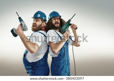 Funny portrait of two cheerful craftsmen - stock photo