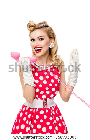 Funny portrait of woman with phone, dressed in pin-up style red dress in polka dot and white gloves, isolated. Caucasian blond model posing in retro fashion and vintage concept studio shoot. - stock photo