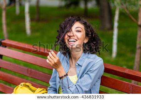 Funny portrait of young attractive smiling brunette fooling around, having fun messing her long hair with happy expression outdoors - stock photo