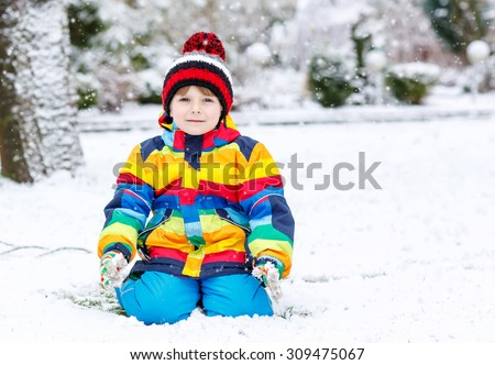 Funny preschool boy in colorful clothes happy about snow, playing and having fun, outdoors during snowfall on cold day. Active outoors leisure with children in winter. - stock photo