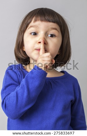 funny preschool girl wanting to keep silent with her finger on lips - stock photo