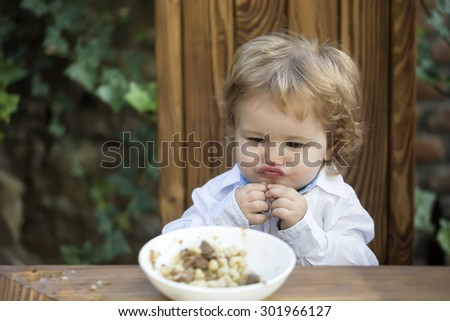Funny pretty little baby boy with blond curly hair with cute expression on face sitting on wooden chair eating cereal for breakfast from plate outdoor on natural green background, horizontal photo - stock photo