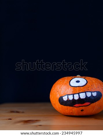 funny pumpkin decorated on black background - stock photo