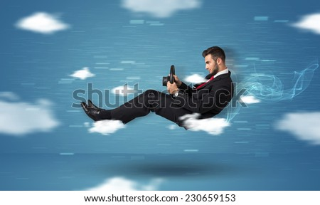 Funny race driver young man driving between clouds concept on blue background - stock photo