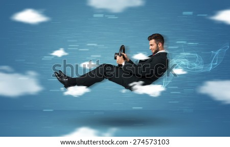 Funny racedriver young man driving between clouds concept on blue background - stock photo