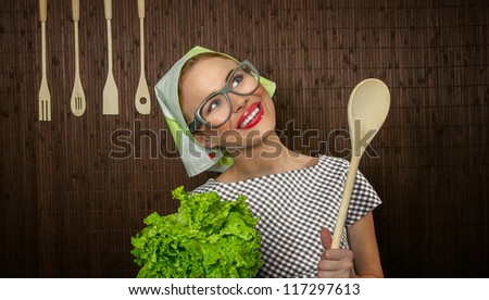 Funny rural woman cook holdin ledle and salad, close-up - stock photo