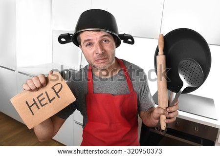 funny 30s Caucasian man holding pan and household with pot on his head in red apron at home kitchen asking for help unable to cook showing panic on cooking with funny face expression - stock photo
