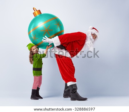 Funny Santa and elf holding together a huge Christmas bauble. - stock photo
