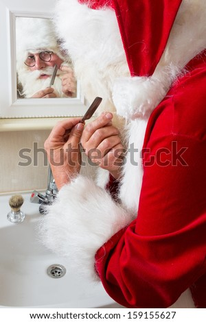 Funny Santa Claus shaving off his mustache and beard - stock photo